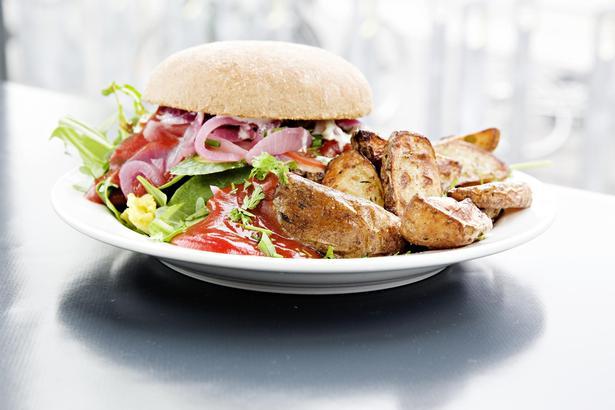 Husets burger er fyldt med sprød agurk, mayo, salatblade, ost og lækre syltede rødløg, og den serveres med stegte kartoffelbåde.
