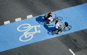 Trafik. Cyklist i blå cykelbane i vejkryds.