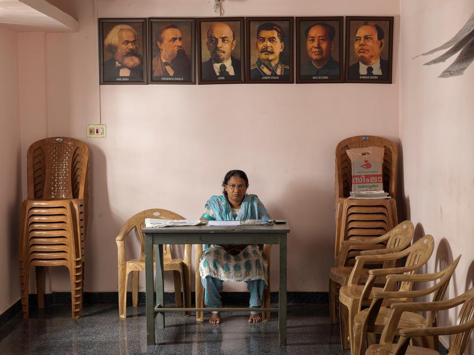 Indien. Shyla K. John, medlem af det mindre kommmunistparti Socialist Unity Centre India (Communist), forkortet SUCI (C). Portrættet af Shibdas Ghosh, der stiftede partiet, hænger side om side med Marx, Engels, Lenin, Stalin og Mao.