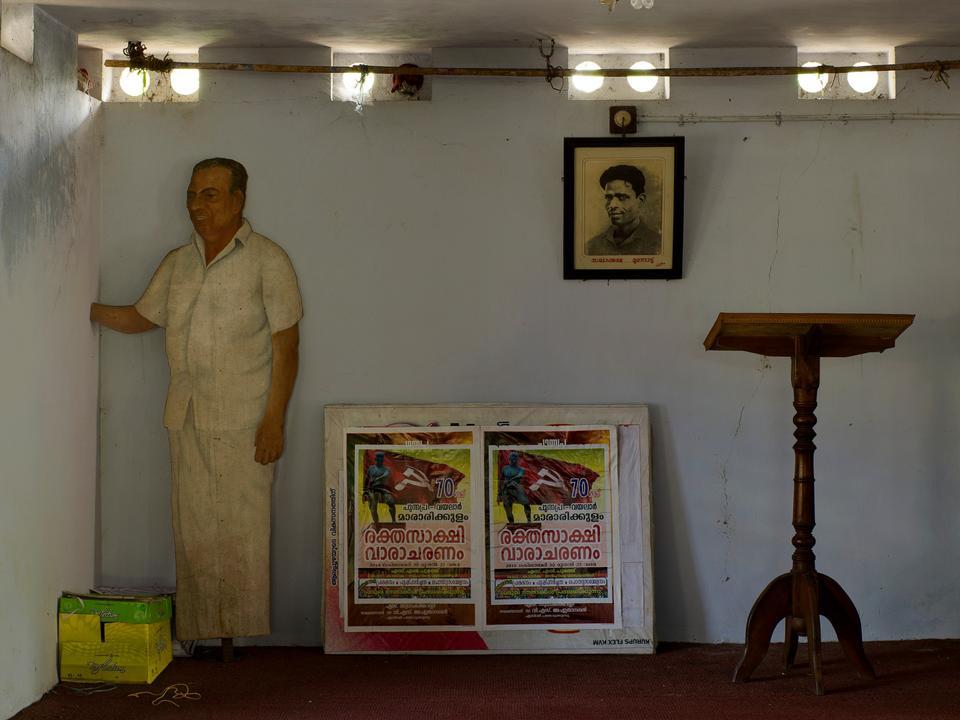 Indien. Et mødelokale tilhørende landets kommunistparti. Papfiguren forestiller den afdøde partileder Ayillayath Kuttiari Gopalan og på portrættet på væggen ses P. Krishna Pillai, digter og grundlægger af regionen Keralas kommunistiske bevægelse.