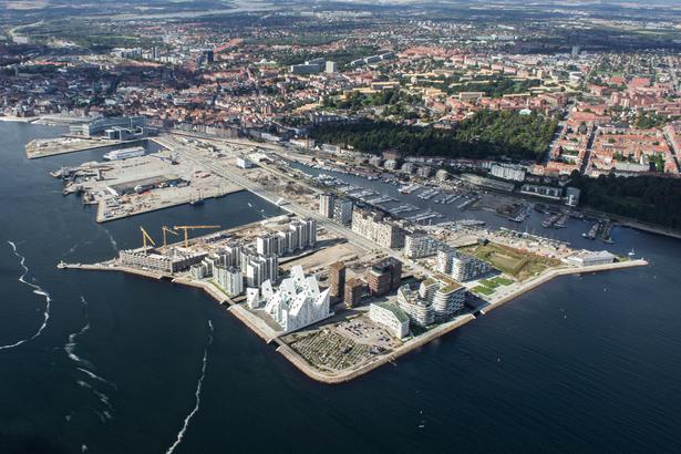 Aarhus Ø september 2017. Til venstre ses Bassin 7 med kranerne, der er ved at opføre AARhus. I hjørnet ligefor ses det midlertidige projekt Ø-haven, som efter planen også får lidt plads, efter Lighthouse 2.0 skyder 142 meter i vejret på pladsen. Til venstre for Ø-haven ligger Isbjerget med de brune pakhuse bagved. Ved siden af Pakhusene ud til vandet ligger Lighthouse 1.0.