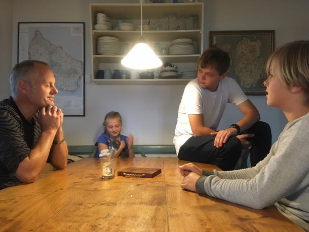 En del af familien Pedersen er samlet rundt om køkkenbordet. Udover far Klaus er Gunhild (9), Eskild (11) og Magnus (19) med i snakken om deres skoletid.