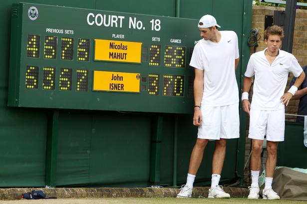 Nicolas Mahut og John Isner efter afgørelsens af deres kamp fra 2010. Samme Isner var også del af en lang, lang femsæts-kamp i Wimbledon i 2018, hvor han tabte til Kevin Anderson efter seks timer og 36 minutters spil. (AP Photo/Alastair Grant, Pool, File)