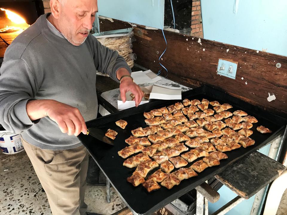 Små brødpakker med kødfyld er klar til at blive spist. I lokalet ved siden af ovnen sidder masser af sultne gæster og venter – det er frokosttid.