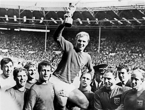 Gordon Banks står yderst til venstre med holdkammerater som f.eks. Alan Ball, Bobby Charlton (yderst th.) og Geoff Hurst, mens anfører Bobby Moore holder VM-trofæet efter triumfen i 1966.