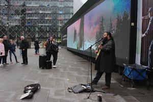Gadeliv i København. Gademusikant spiller guitar på Rådhuspladsen.
