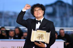 """TOPSHOT - South Korean director Bong Joon-Ho celebrates during a photocall after he won the Palme d'Or for the film """"Parasite (Gisaengchung)"""" on May 25, 2019 during the closing ceremony of the 72nd edition of the Cannes Film Festival in Cannes, southern France. (Photo by LOIC VENANCE / AFP)"""