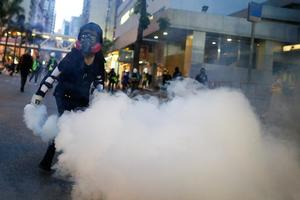An anti-extradition bill protester throws a tear gas cartridge back at police during clashes in Wan Chai in Hong Kong, China August 11, 2019. Picture taken August 11, 2019. REUTERS/Thomas Peter