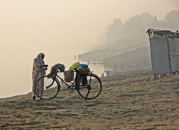 I Varanasi ved Ganges-floden holder en person rast i det fineste morgenlys.