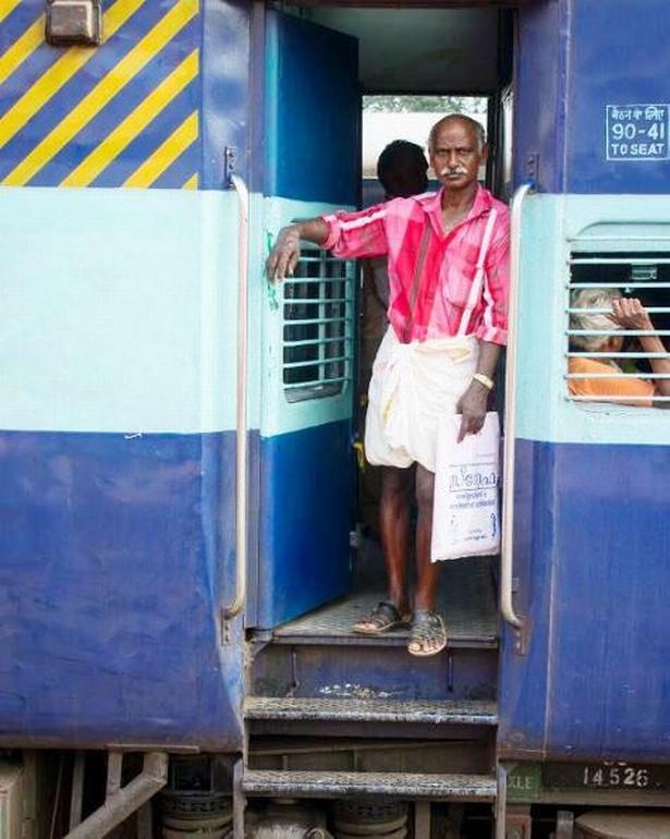 En mand kigger ud af et tog på Thiruvananthapuram Central Railway Station i Indien.