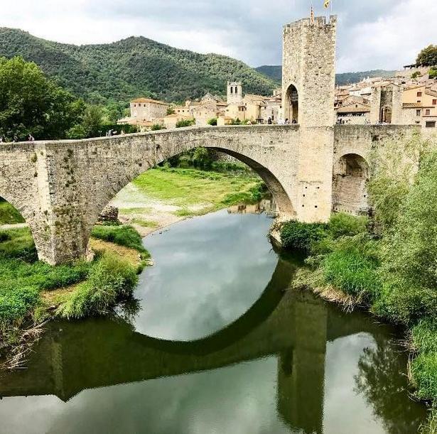 Middelalderbroen i Besalú nær Costa Brava i Spanien spejler sig smukt i vandet.