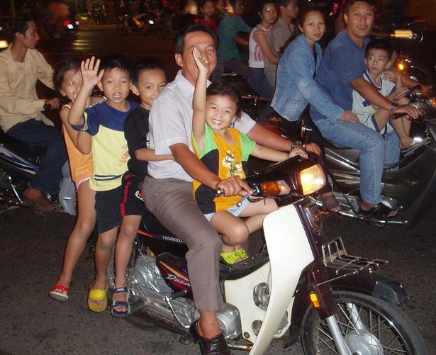 Far med sine fire børn på aftentur i Ho Chi Minh i Vietnam.